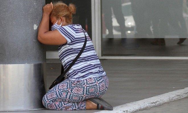 Mulher chorando a morte de um parente vítima de Covid-19
