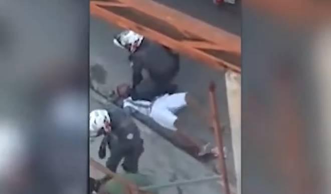 Policial com os joelhos no peito de homem durante abordagem