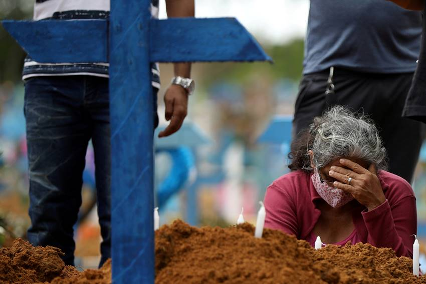 Pessoa chorando a morte de parente vítima da Covid-19 — © Reprodução