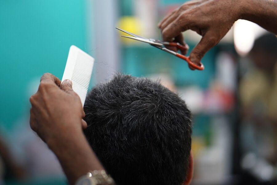 Homem cortando o cabelo de cliente - imagem ilustrativa