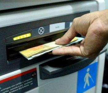 Pessoa sacando dinheiro em caixa eletrônico — © Reprodução
