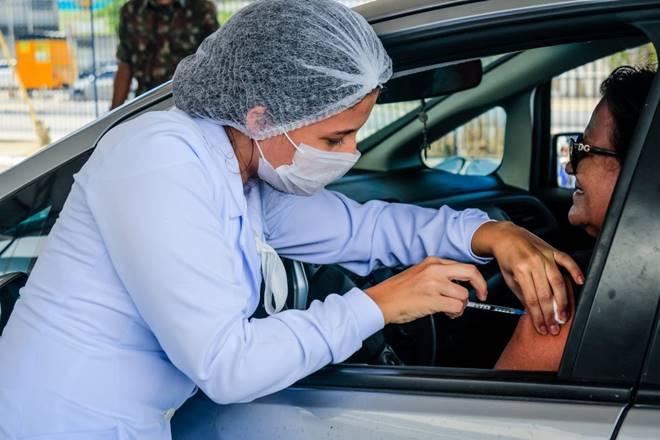 Enfermeira vacinando idosa no drive-thru em Maceió — © Secom Maceió