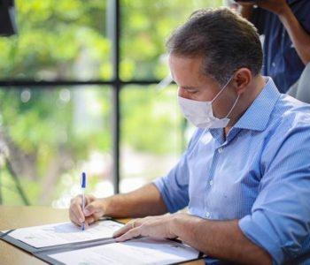 Governador Renan Filho assinando documento — © Assessoria