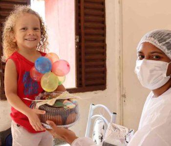 Criança recebendo presente de assistente social –© Assessoria