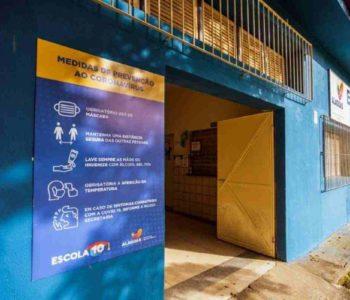 Placa com medidas de prevenção à Covid colocada na porta de escola no Cepa — © Agência Alagoas