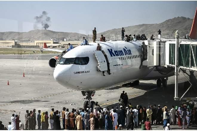 Afegãos são vistos em cima de avião após multidão invadir aeroporto de Cabul na tentativa de fugir do Talibã –©  Wakil Kohsar / AFP