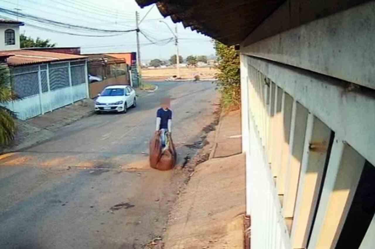 Homem arrastando um grande saco, envolto em um cobertor, em plena luz do dia | © Reprodução