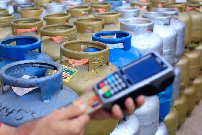 Trabalhador inserindo cartão em maquineta na compra de botijão de gás – © Myke Sena
